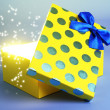 Gift box with bright light on it on blue background — Stock Photo #36974117