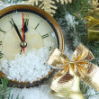 Clock with fir branches and Christmas decorations under snow close up — Stock Photo #36974541