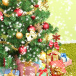 Decorated Christmas tree with gifts on green wall background — Stock Photo #36982269
