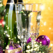 Composition with Christmas decorations and two champagne glasses, on bright background — Stock Photo #36982313