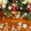 Beautiful Christmas decorations on fir tree on wooden background — Stock Photo