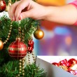 Decorating Christmas tree on bright background — Stockfoto