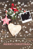 Decorative heart, star and empty photo paper on rope, on wooden background — Zdjęcie stockowe