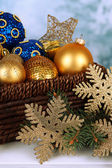 Christmas decorations in basket and spruce branches on table on bright background — Stock Photo