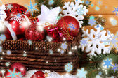 Christmas decorations in basket with snow on table on wooden background — Stock Photo