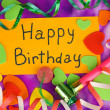 Card Happy Birthday surrounded by festive elements on purple background — Stok fotoğraf