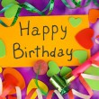 "Card ""Happy Birthday"" surrounded by festive elements on purple background — Stock Photo"