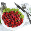 Beet salad on plate on napkin on wooden board isolated on white — Stock Photo #37013113