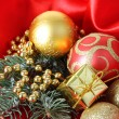 Beautiful Christmas decor on red satin cloth — Stock Photo #37013179