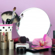 Round table mirror with cosmetics and flower on table on violet background — Foto de Stock