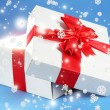 Gift box with bright light on it on blue background — Stok fotoğraf