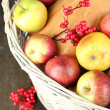 Juicy apples and pumpkin in wooden basket on table close-up — Stock Photo
