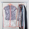 Stock Photo: Office female clothes in cases for storing on hangers, on gray background