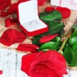 Beautiful red rose with ring on wooden table close-up — Stock Photo #37014211