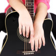 Acoustic guitar in female hands, isolated on white — Stock Photo