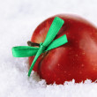 Red apple with bow in snow close up — Stock Photo
