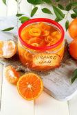 Oranžový jam s kůrou a mandarinky, na bílý dřevěný stůl — Stock fotografie
