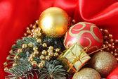 Beautiful Christmas decor on red satin cloth — Stock Photo