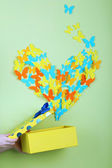 Paper butterflies fly out of box on green wall background — Stock Photo