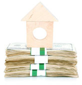 Wooden house on packs of dollars isolated on white — Stock Photo