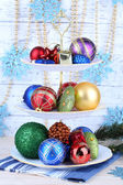 Christmas decorations on dessert stand, on color wooden background — Stock Photo