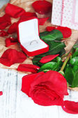 Beautiful red rose with ring on wooden table close-up — Foto Stock