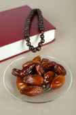 Composition with holy book,rosary and dates palm, on gray background — Stock Photo