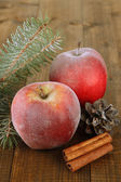 Red frosted apples with fir branch and bumps on wooden background — 图库照片