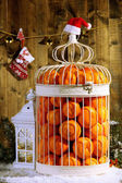 Tangerines in decorative cage with Christmas decor, on wooden background — Stockfoto