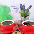 Red cups of strong coffee with cookies and flowers on bamboo mat on bright background — Stock Photo #37031105