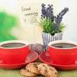 Red cups of strong coffee with cookies and flowers on bamboo mat on bright background — Stock Photo