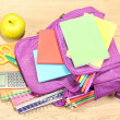 Purple backpack with school supplies on wooden background — Stock Photo #37031817