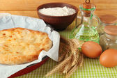 Pita bread in oven-tray with spices on tablecloth on wooden background — Stock Photo
