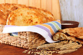 Pita breads in basket with spikes and flour on table on wooden background — Stock Photo