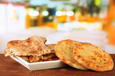 Pita breads on tray on table on bright background — Stock Photo