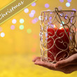 Stock Photo: Candle in hand on blur lights background