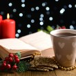 Stock Photo: Composition of book with cup of coffee and Christmas decorations on table on dark background