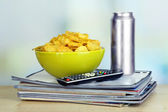 Chips in bowl, beer and TV remote on wooden table on room background — Stock Photo