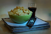 Chips in bowl, cola and TV remote on wooden table on room background — Stock Photo