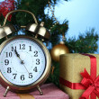 Alarm clock with Christmas tree and presents on table on blue background — Stockfoto