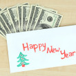 Dollar bills in envelope as gift at New year on wooden table close-up — Stock Photo #37078089