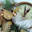 Clock with fir branches and Christmas decorations under snow close up — Stock Photo #37078173