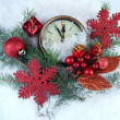 Clock with fir branches and Christmas decorations under snow close up — Stock Photo #37078181
