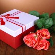 Beautiful gift box with flowers on table on brown background — Stock Photo #37078201