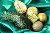 Beautiful Christmas decor on green satin cloth — Stock Photo