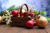 Složení s vánoční ozdoby v košíku, jedle na dřevěný stůl, na světlé pozadí — Stock fotografie