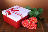 Beautiful gift box with flowers on table on brown background — Stock Photo