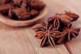 Star anise in wooden spoon, on wooden background — Stock Photo