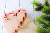 Christmas candy canes and letters for Santa, on color wooden background — ストック写真