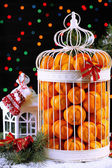 Tangerines in decorative cage with Christmas decor, on shiny background — ストック写真